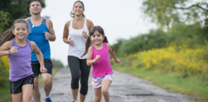 A family of four is going on a run together outside in nature. They are running down the road and are smiling while looking at the camera.